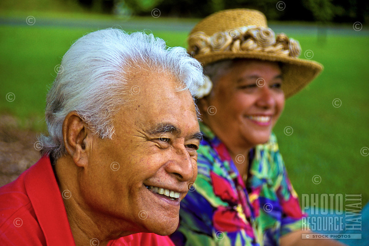 Smiling senior Hawaiian man and part-Hawaiian woman with hat