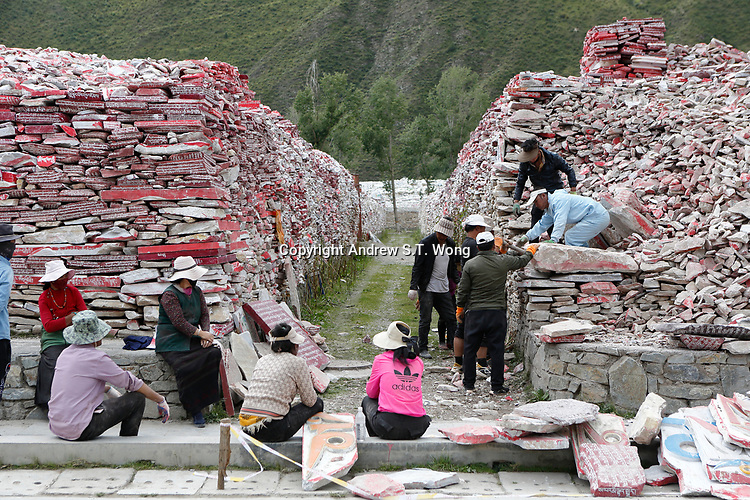 Yushu City, Yushu Tibetan Autonomous Prefecture, Qinghai Province, China -Tibetans rearrange mani stones at Yushu Jiana Mani stone mound which is the largest in the world, August 2019. Now it has around 200 million stones, is 300 meters long, 3 meters high, and 80 meters wide.