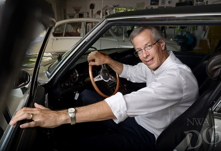 STAFF PHOTO BEN GOFF  @NWABenGoff -- 08/28/14 Bill Watkins, president of the British Iron Touring Club, poses for a photo in his 1973 Jensen Interceptor in the garage at his Rogers home on Thursday August 28, 2014. The touring club will hold it's 13th annual 'Brits in the Ozarks' show at Agri Park in Fayetteville on September 13 as a fundraiser for the ALS Association Arkansas chapter.
