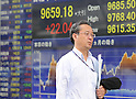 August 4, 2011, Tokyo, Japan - A man walks past a stock market indicator board, August 4, 2011, in Tokyo, Japan. The U.S. dollar staged a strong rebound to near 80 yen. The Finance Ministry and the Bank of Japan intervened August 4 in the foreign exchange market, selling a huge amount of yen to purchase the U.S. dollar, the first such move by the country since March. Japan is heavily dependent on exports for generating even the meagre economic growth of the past few years. The Japanese currency has been getting stronger since the March 11 earthquake and tsunami. The Japanese export industry, a global manufacturing and export base, is influenced for the worse by a strong yen. (Photo by Tomoyuki Kaya/AFLO) [3694]