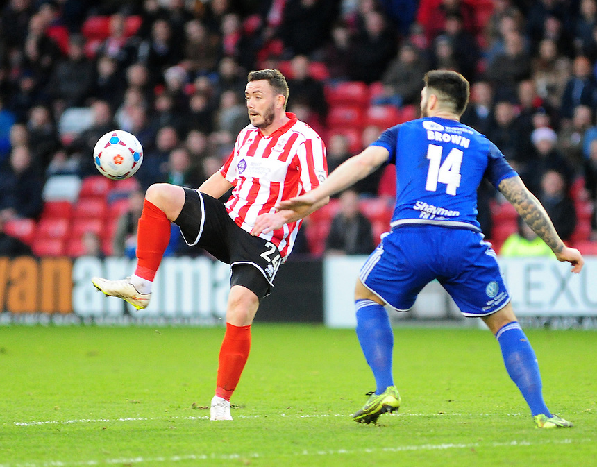 Lincoln City&rsquo;s Craig Reid lifts the ball over FC Halifax Town's Matty Brown<br /> <br /> Photographer Andrew Vaughan/CameraSport<br /> <br /> Football - Vanarama National League - Lincoln City v FC Halifax Town - Saturday 26th December 2015 - Sincil Bank - Lincoln<br /> <br /> &copy; CameraSport - 43 Linden Ave. Countesthorpe. Leicester. England. LE8 5PG - Tel: +44 (0) 116 277 4147 - admin@camerasport.com - www.camerasport.com