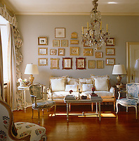 A collection of small sketches and prints covers the wall above a comfortable sofa in this elegant sitting room