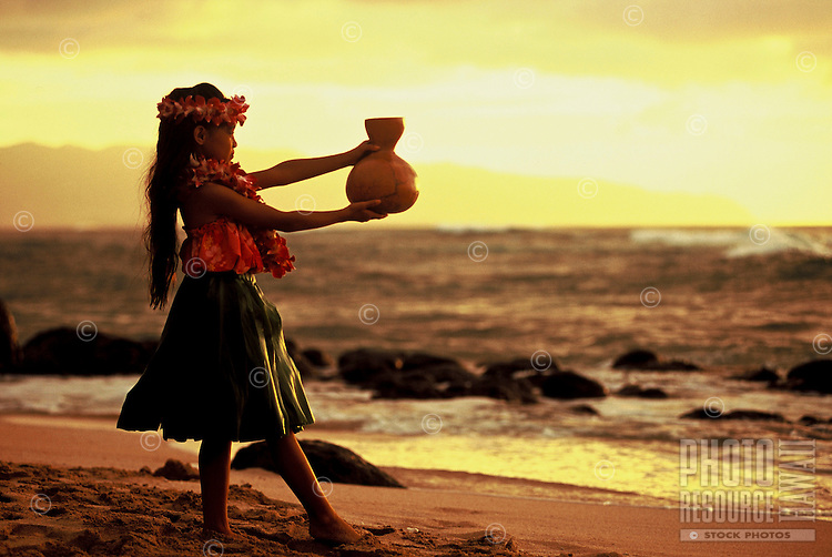 Young Hawaiian girl (age 7) dancing hula with an ipu (gourd) on the beach at sunset