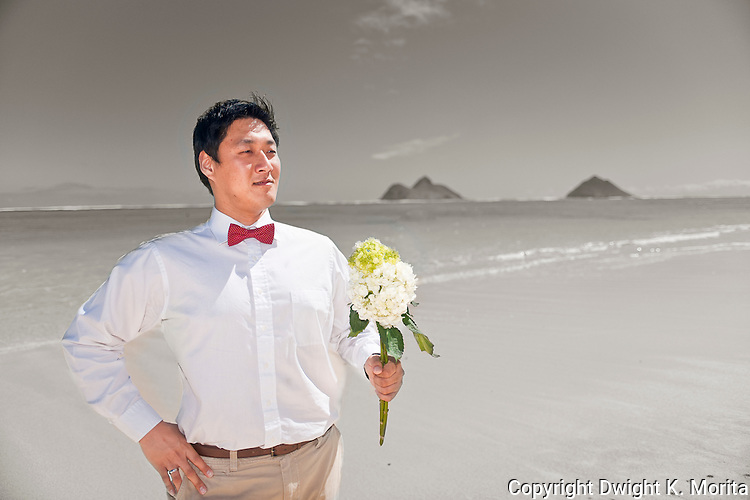 Asian groom waits for his bride with a bouquet of flowers during a stroll on Lanikai beach as they look forward to their life as a married couple following their wedding. Color and BW cutout.
