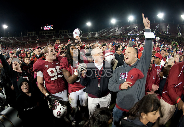 STANFORD, CA-NOVEMBER 27, 2010-Stanford University President John John Hennessy, center, Richard Sherman, and Brian Bulke, left, lead the crowd in song after the Stanford 38-0 victory over Oregon St., Saturday, November 27, 2010.