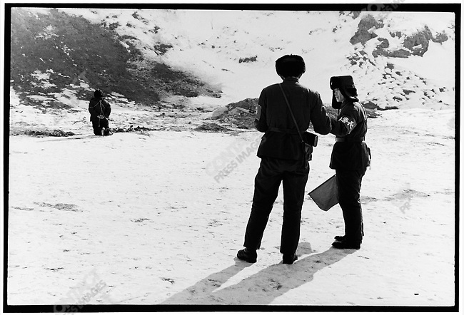 A guard hands a single bullet to Wang Shouxin's executioner. Outskirts of Harbin, 8 February 1980