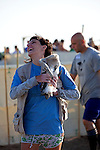 Volunteer carrying a chick to be released at the annual Flamingo round up and leg ringing event, in Fuente de Piedra lagoon, Andalucia, Spain