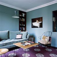 The blue of the walls and the mauve rug give the living room a cool ambiance. The room is simply furnished with furniture in a mix of styles