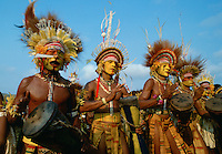 Tribesman musicians wearing war paints, feathered headdresses and necklaces made of bones and teeth playing drums and chanting during  a gathering of tribes at Mount Hagen in Papua New Guinea