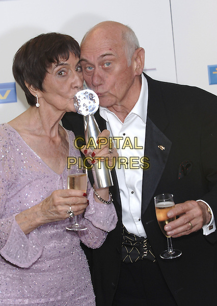 JUNE BROWN & JOHN BARDON.British Soap Awards - Press Room.BBC Television Centre, W12, London.May 7th, 2005.Ref: PL.half length award trophy kissing gesture champagne drink.www.capitalpictures.com.sales@capitalpictures.com.©Capital Pictures.