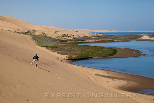 Hiker on sand dunes overlooking Sandwich Harbour, Namibia.