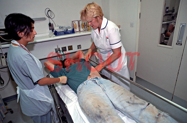 A vagrant being attended to in the crash room of an A&E department in a hospital. The nurses are removing his clothes so as to be able to assess his injuries and his condition. This image may only be used to portray the subject in a positive manner..©shoutpictures.com..john@shoutpictures.com