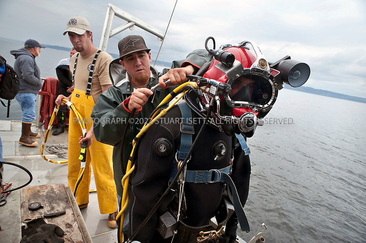 8/14/2009--Puget Sound, Seattle, WA, USA..Jeromy Meyer (right) prepares to dive to remove nets from Puget Sound. Center: Jake Johnston, left: Chris Melson: all divers with  Nisqually Aquatic Technologies...Jeff Choke, a member of the Nisqually Indian tribe in Washington State, and director of marketing for Nisqually Aquatic Technologies, a  diving company, has been hired using federal stimulus dollars to remove old nets in Puget Sound that destroy habitat and kill fish and other marine animals. The Nisqually indians are one of many tribes whose fishing has been affected by the big commercial fishing nets that came to deplete fish populations and damage the Sound....©2009 Stuart Isett. All rights reserved.