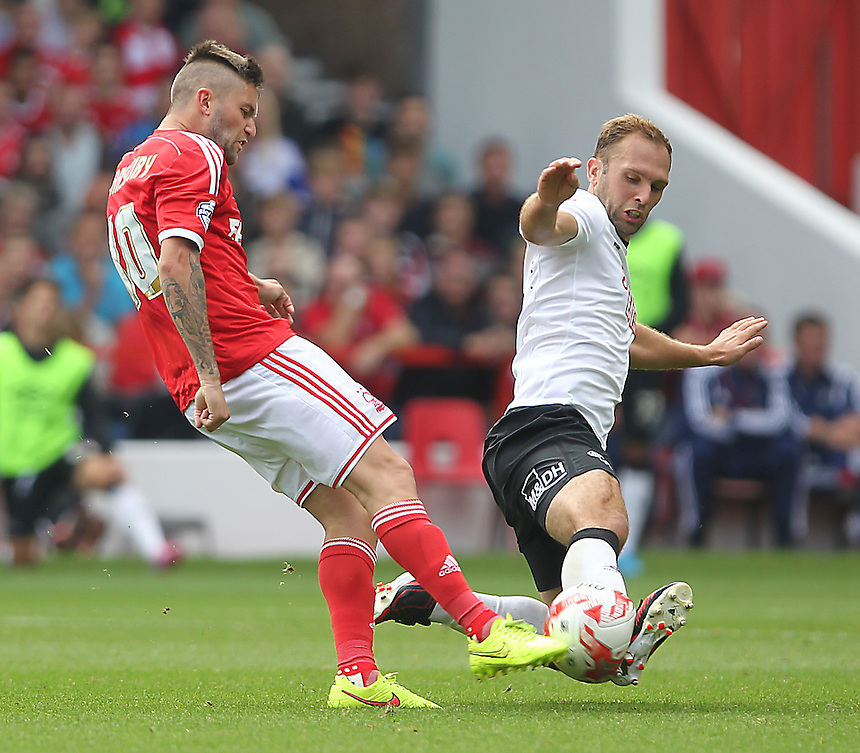 Derby County's John Eustace blocks a shot from Nottingham Forest's Henri Lansbury<br /> <br /> Photographer Mick Walker/CameraSport<br /> <br /> Football - The Football League Sky Bet Championship - Nottingham Forest v Derby County - Sunday 14th September 2014 - The City Ground - Nottingham<br /> <br /> &copy; CameraSport - 43 Linden Ave. Countesthorpe. Leicester. England. LE8 5PG - Tel: +44 (0) 116 277 4147 - admin@camerasport.com - www.camerasport.com