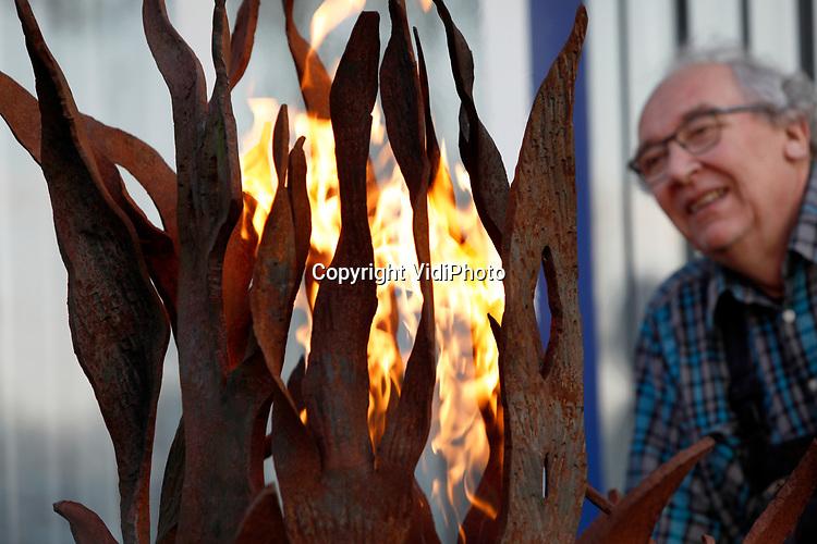 Foto: VidiPhoto<br /> <br /> ANDELST - Het vrijheidsvuur brandt dit jaar niet in Wageningen, maar in de Betuwe. Vaksmid Cees Pronk installeert zaterdagavond in Andelst het kunstwerk Flame of Freedom, als alternatief voor de jaarlijkse ceremonie in Wageningen dat dit jaar vanwege de coronacrisis niet doorgaat. De oud-Wageninger heeft daarom dit initiatief naar zich toe getrokken door een vrijheidskunstwerk te maken van stalen vlammen, met aan de voorzijde gesmede koperen klaprozen. Deze zogenoemde poppies zijn het internationale symbool dat gebruikt wordt voor het herdenken van gesneuvelde militairen. Flame of Freedom wordt maandagavond 4 mei om 21.00 uur aangestoken. Pronk hoopt dat zijn 'vrijheidsmonument' volgend jaar in Oosterbeek wordt gebruikt bij de de herdenking van 76 jaar vrijheid.