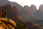 A young man rides his mountain bike on slickrock near Sedona, Arizona.