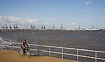 Man cycling on the seafront at Harwich, Essex, England with the Port of Felixstowe in the background