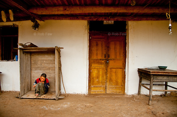 A disabled child in a village in Sichuan, China, that was badly affected by the 2007 earthquake. <br /> <br /> The Red Cross has helped to rebuild houses and is now putting in running water, making life easier for families.