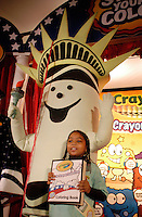 """BROOKLYN HEIGHTS, NY - OCTOBER 26: Tracy Ceschin (L), of New York City, New York portraying the New York state color Crayola crayon """"Lady Liberty"""" is walked onto stage by Georgi Forrest, 8, of Brooklyn, New York during the Crayola State Crayons introduction ceremony at PS8 Tuesday October, 26, 2004 in Brooklyn Heights, New York. Earlier this year, Crayola constituents of all ages nominated existing crayon colors and gave them new state-themed names that draw attention to something special about every state in the union. Fifty winners were selected by Crayola from more then 25,000 names entered. """"Boston Tea Party"""" for Massachusetts and """"Alamo a la mode"""" for Texas represent the Presidential candidates home states.(Photo by William Thomas Cain/photodx.com)"""