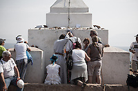 A frair blessing faithful at the foot of the  cross on top of the Mt. Krizevac.<br /> Medjugorje, Bosnia and Herzegovina. July 2012
