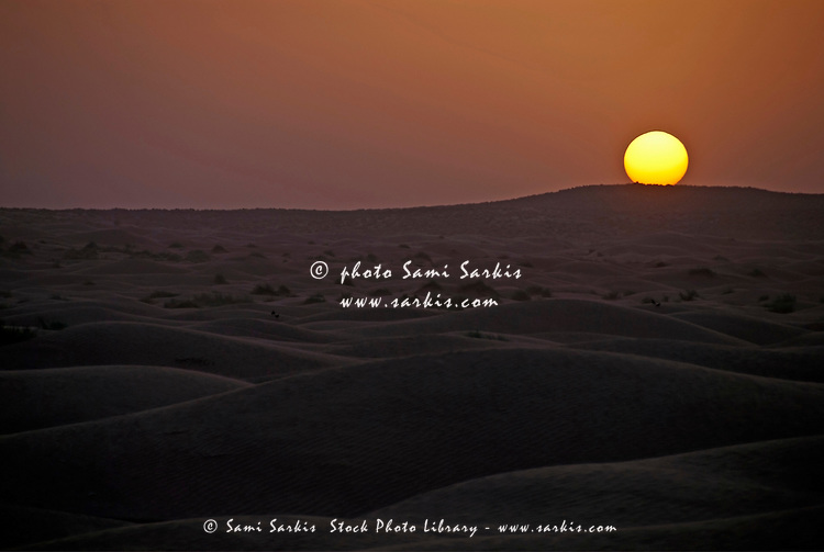 Sun setting behind the sand dunes of the Sahara Desert, Ksar Ghilane, Tunisia.