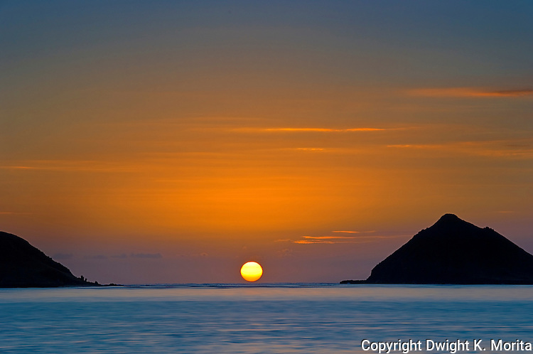 Fireball sunrise emerges from the ocean between the Mokulua Islands at Lanikai Beach