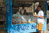 MUS, Mauritius, Cap Malheureux: Tourist mit frischer, geschaelter Ananas vom Kiosk | MUS, Mauritius, Cap Malheureux: tourist with fresh pineapples