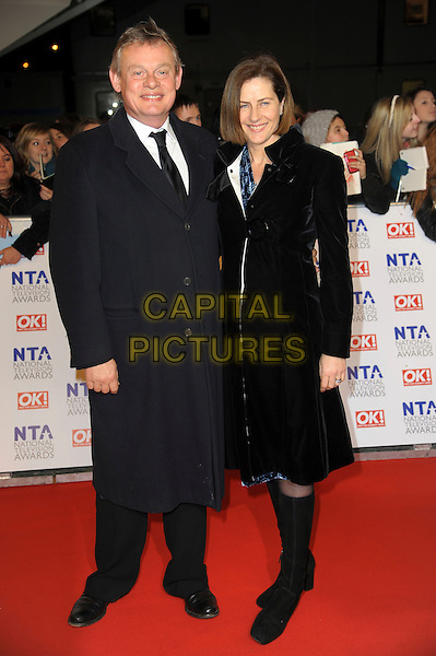 Martin Clunes & guest.arrivals at The National Television Awards, O2 Greenwich, London, England. 25th January 2012.NTA NTAS full length black coat boots.CAP/CAS.©Bob Cass/Capital Pictures.