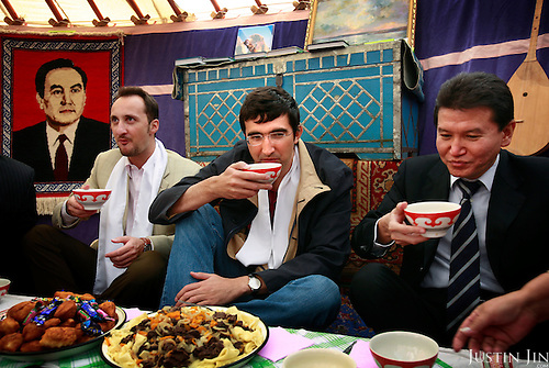 Kirsan Ilyumzhinov (right), 44, president of the southern Russian republic Kalmykia, drinks tea in a yurt with chess grandmasters Veselin Topalov (left) and Vladimir Kramnik (center)...Ilyumzhinov, who is also the president of the World Chess Federation, Fide, is hosting one of the world?s most important matches in history. ..The match beginning September 21 in Elista, the capital of Europe?s only Buddhist nation, will end a 13-year split in the game that has produced rival claims to the title. ..Topalov, a Bulgarian ranked first according to Fide, will play against Kramnik, who is the Classical Chess World Champion, a title established after Garry Kasparov led a breakaway from Fide in 1993. The two grandmasters, both aged 31, will face each other for the right to be undisputed world chess champion...A Buddhist millionaire businessman, Ilyumzhinov acquired his wealth in the economic free-for-all which followed the collapse of the Soviet Union. ..At the age of just over 30, he was elected president in 1993 after promising voters $100 each and a mobile phone for every shepherd. Soon after, he introduced presidential rule, concentrating power in his own hands. ..He denies persistent accusations of corruption, human rights abuses and the suppression of media freedom. When Larisa Yudina, editor of the republic's only opposition newspaper and one of his harshest critics, was murdered in 1998, he strenuously rejected allegations of involvement. ..Mr Ilyumzhinov has been president of the International Chess Federation (FIDE) since 1995 and has been enthusiastic about attracting international tournaments to Kalmykia. His extravagant Chess City has led to protests by its impoverished citizens..