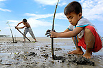 In this 2007 photo from the coastal village of Moawo, 5-year old Jefrin Zendrato (right) and his 10-year old brother Fajrin plant mangrove seedlings, part of a project on the Indonesian island of Nias to improve habitat for sea life and provide some protection from future tsunamis. The project is sponsored by the Yakkum Emergency Unit (YEU), a member of the ACT Alliance.<br /> <br /> Parental consent obtained.