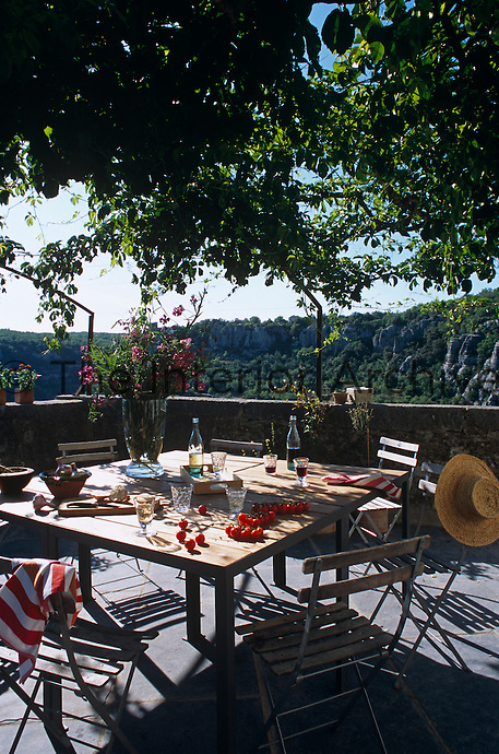 A simple table on the vine-covered roof terrace overlooks the dramatic Ardeche river gorge