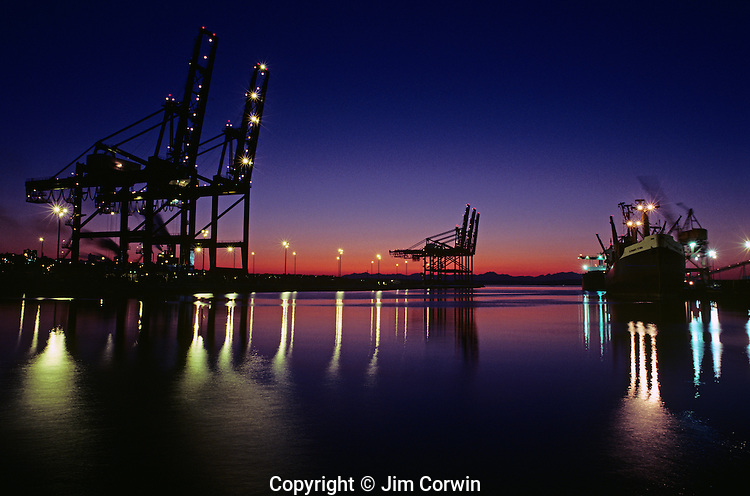 Port of Tacoma at sunset with large cranes in a row unloading tanker moored at dock Tacoma waterfront Tacoma Washington State USA.