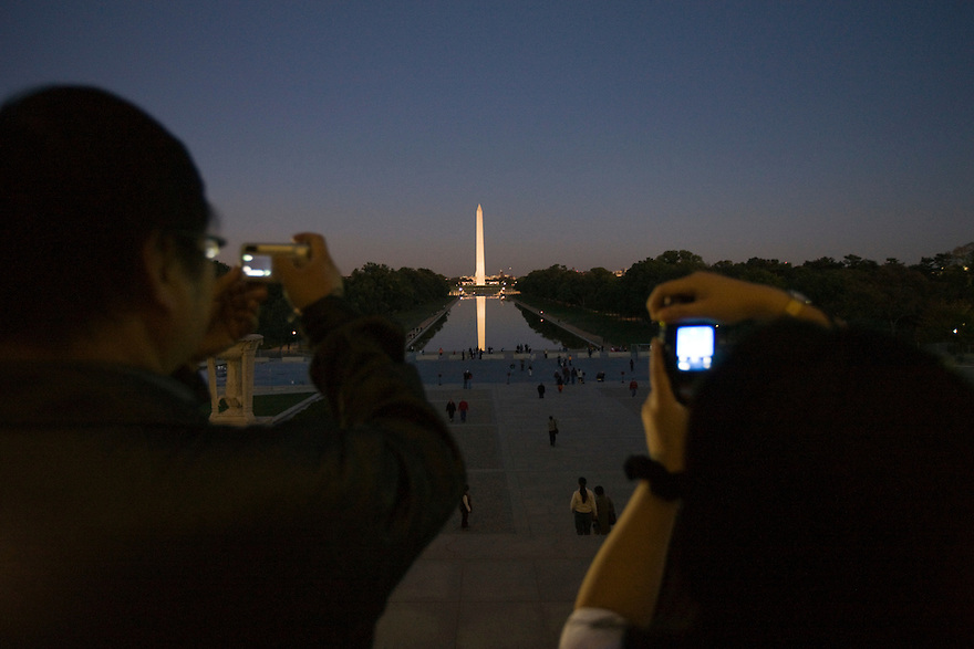 Tourists photograph the Washington Monument from the steps of the Lincoln Memorial in Washington, DC...Photo by Brooks Kraft/Corbis........