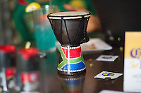 Hartford, CT - Friday June 13, 2014: A small African drum with the Cameroon flag on it sits on the table where Cameroonian Joyce Ashuntantang watches the Cameroon vs. Mexico FIFA World Cup first round match with her son's at Damons Tavern in Hartford, CT.