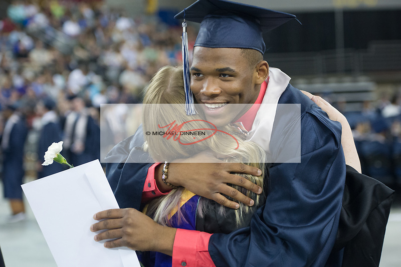 0575<br /> <br /> Eagle River graduate Chris Eckles, who sang from the stage during the ceremonies, gets a hug from a faculty member.  Photo for the Star by Michael Dinneen.