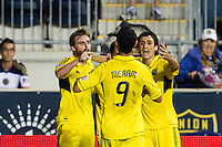 Eddie Gaven (12) of the Columbus Crew celebrates scoring with Justin Meram (9) and Milovan Mirosevic (10). The Columbus Crew defeated the Philadelphia Union 2-1 during a Major League Soccer (MLS) match at PPL Park in Chester, PA, on August 29, 2012.