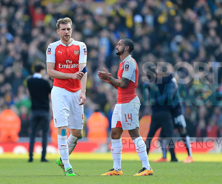 Arsenal's Per Mertesacker and Theo Walcott look on dejected at the final whistle during the Emirates FA Cup match at The Emirates Stadium.  Photo credit should read: David Klein/Sportimage