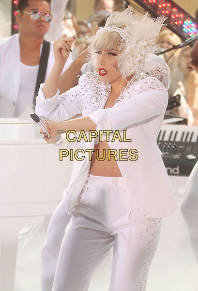 "LADY GAGA (Stefani Joanne Angelina Germanotta) .performs live on NBC's ""TODAY"" Show at Rockefeller Center, New York, NY, USA, 9th July 2010..on stage music concert gig half length white microphone funny dancing suit jacket bra feather lace ear muffs head band hair hairband silver beaded studded embellished hand .CAP/ADM/AC.©Alex Cole/AdMedia/Capital Pictures."