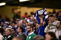 A France fan in the crowd holds up a scarf in support. Rugby World Cup Pool D match between France and Ireland on October 11, 2015 at the Millennium Stadium in Cardiff, Wales. Photo by: Patrick Khachfe / Onside Images
