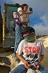 Two Israeli peace activists, one of whom is chained to an Israeli bulldozer at a construction site for Israel's controversial West Bank barrier in the village of Al Walaja on 09/06/2010. Two Israelis & one Palestinian - Dr Marin Qumsiyeh - were arrested by border police.