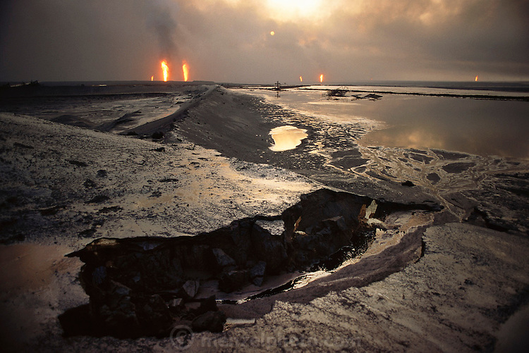 An oil lake and devastated desert landscape in the burning greater Al Burgan oil fields in Kuwait after the end of the Gulf War in May of 1991. More than 700 wells were set ablaze by retreating Iraqi troops creating the largest man-made environmental disaster in history.