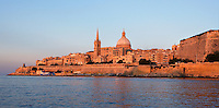 General view of Valletta,  Malta from the sea, featuring the dome of the Carmelite Church, 1573, and spire of St Paul's Anglican Pro-Cathedral, 1839-44, pictured on June 6, 2008, in the warm evening light.  The Republic of Malta consists of seven islands in the Mediterranean Sea of which Malta, Gozo and Comino have been inhabited since c.5,200 BC. Nine of Malta's important historical monuments are UNESCO World Heritage Sites, including  the capital city, Valletta, also known as the Fortress City. Built in the late 16th century and mainly Baroque in style it is named after its founder Jean Parisot de Valette (c.1494-1568), Grand Master of the Order of St John. The Carmelite church was originally built by Gerolamo Cassar, and rebuilt after bomb damage during World War II.  St Paul's Anglican Pro-Cathedral was designed by William Scamp. To the right of the image are the Ramparts. Picture by Manuel Cohen.