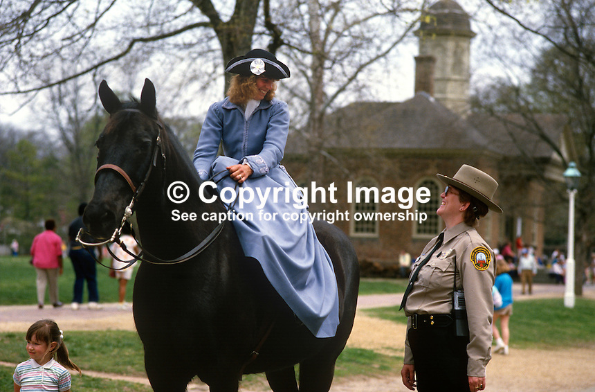Horsewoman riding side-saddle and in 18th century attire out for a canter meets present day security woman complete with walkie-talkie in Colonial Williamsburg Historic Area, the restored capital of 18th century Virginia. 19880505CW12.<br />