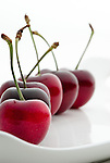 Red cherries line up in a white plate