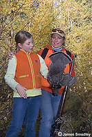 Young girl hunter beside her mother holding shot ruffed grouse