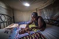 Uganda, Seeta. Ann Nankya has the Wowsolar power system that she uses to charger her radio and lights. She uses the light to bath her baby in the evening.
