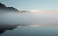 Lake Mapourika foggy sunrise and Southern Alps in background, Westland Tai Poutini National Park, West Coast, UNESCO World Heritage Area, New Zealand, NZ