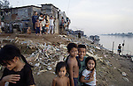 Phnom Penh, Cambodia.  November 1, 2003. Streets of Phnom Penh.      Residents of Chabampau,  a shanty town on the Mekong,  and one of the poorest areas of the city.    Cambodians wash their bodies and clothes in the muddy river as the sun sets.    (PHOTO  by Ellen Jaskol/Rocky Mountain News)