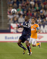 New England Revolution defender Cory Gibbs (12) controls the ball as Houston Dynamo midfielder Danny Cruz (5) closes. The New England Revolution defeated Houston Dynamo, 1-0, at Gillette Stadium on August 14, 2010.