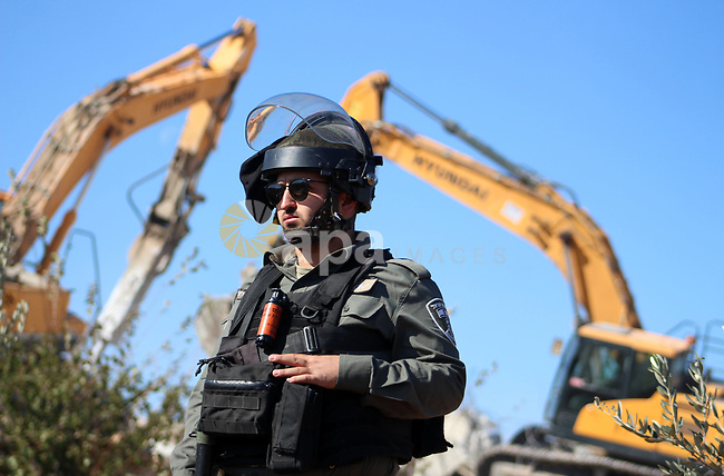 Israeli border police guard as Israeli bulldozer demolishes a Palestinian building which does not have the Israeli needed permits at al-Aroub camp north of Hebron in the southern West Bank on November 19, 2019. Israeli forces regularly target Palestinian residents and their properties in that area by demolishing their homes and seizing their lands. Photo by Mosab Shawer